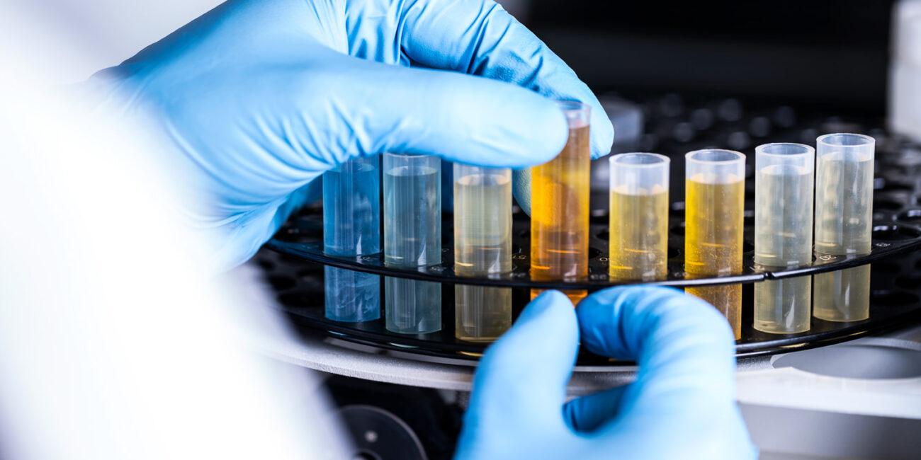 Foto corporate di azienda in laboratorio con mani e provette di liquidi vari