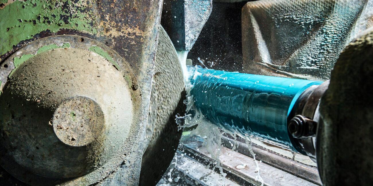 Foto corporate di azienda in fabbrica con fresa e macchinario meccanico a rullo con acqua