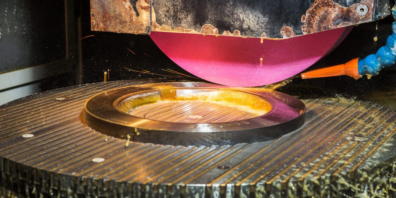 Foto corporate di azienda in fabbrica con fresa e macchinario meccanico a ruota acqua e scintille