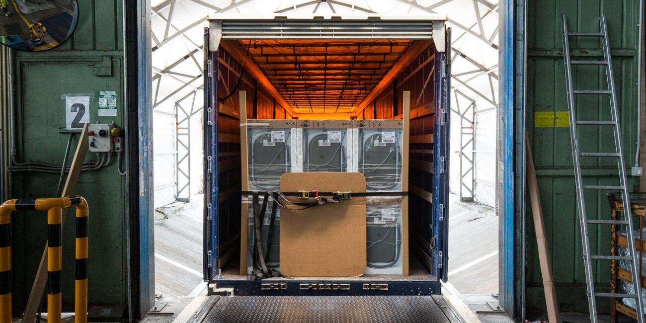 Foto corporate di azienda in fabbrica con lavatrici imballate che vengono caricate nel camion